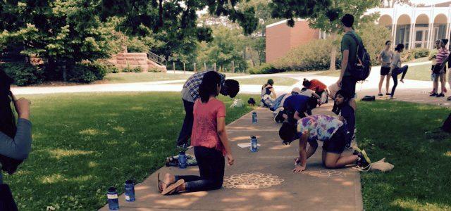 Kids draw on a sidewalk with chalk.