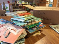 A stack of books sitting at a book donation.