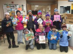 Young children proudly brandish their newly obtained books for the camera to see.