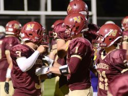 The Northfield High School football team celebrates on field after a successful play.